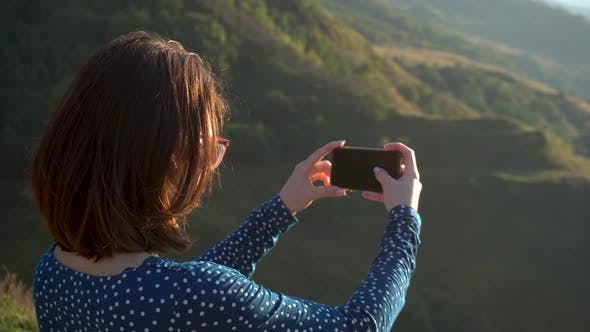 Thumbnail for A Young Woman in a Dress Stands in the Mountains and Takes Pictures on the Phone. The Girl Travels