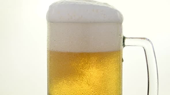 Pouring fresh lager beer in big glass mug over white background