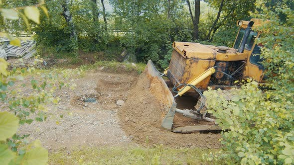 Thumbnail for a Bulldozer Levels and Repairs a Road in the Mountains. The Bulldozer Moves Slowly and Covers the