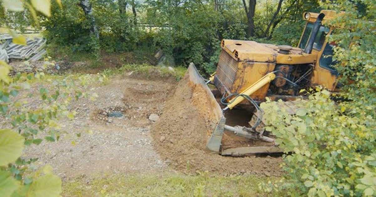 a Bulldozer Levels and Repairs a Road in the Mountains. The Bulldozer Moves Slowly and Covers the