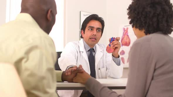 Hispanic cardiologist talking to couple using heart model