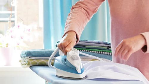 Female Hands Ironing Clothes with Iron on Ironing Board