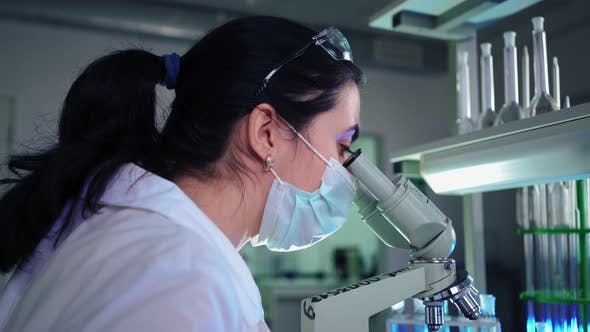 Thumbnail for Female Microbiologist Looking Into Microscope in Medical Science Laboratory