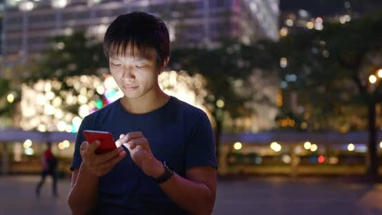 Thumbnail for Asian Man use of mobile phone in city of Hong Kong at night