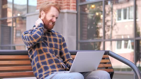 Cover Image for Redhead Beard Young Man with Neck Pain Using Laptop Outdoor