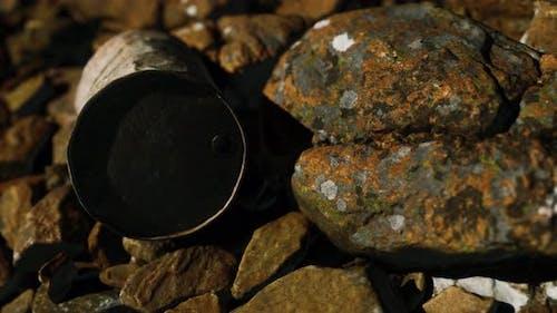 Rusty Destroyed Metal Barrel on Beach Rocks