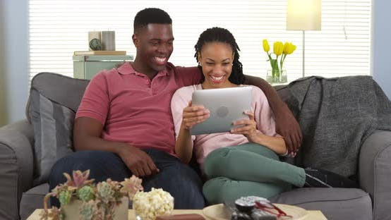 Thumbnail for Happy young black couple laughing and using tablet computer on sofa