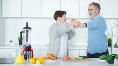 Joyful Couple of Retirees Dancing in Kitchen at Home