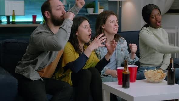 Gruppe gemischter Menschen, die zu Hause Sport im Fernsehen schauen