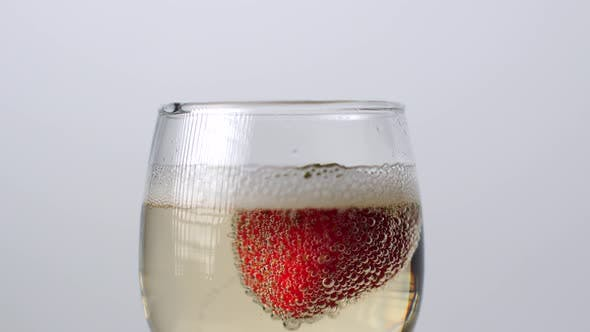 Close-up View of Strawberry Falling Into a Glass of Champagne on a White Background