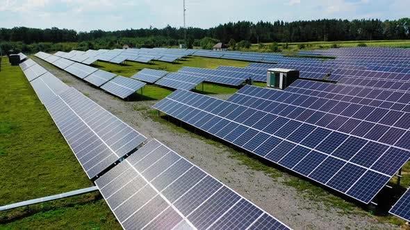 Flight near blue solar batteries in the field. Contemporary electricity farm