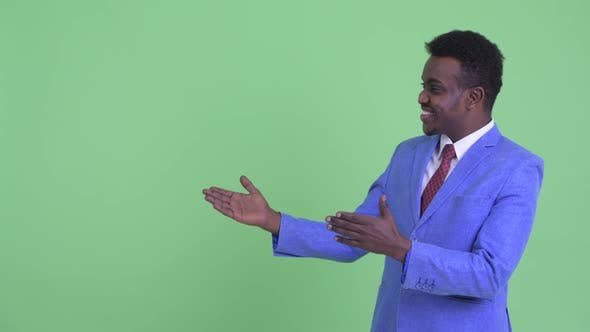 Thumbnail for Happy Young African Businessman Showing Something and Looking Excited