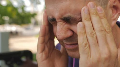 Closeup of a Man Massaging His Temples As a Result of a Headache Outside in a Park