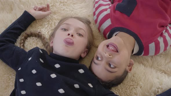 Thumbnail for Portrait African American Boy and Blond Caucasian Girl Lying on the Floor on the Beige Fluffy Carpet