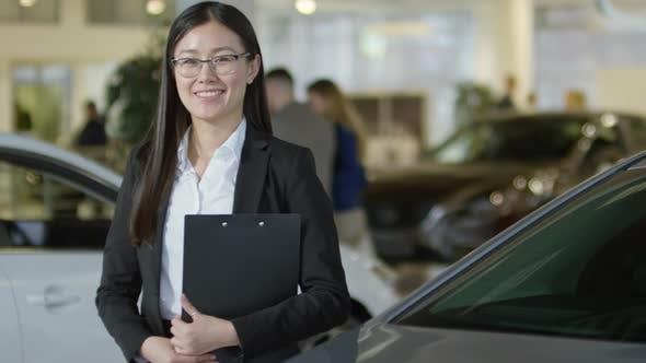 Thumbnail for Saleswoman Posing at Car Dealership