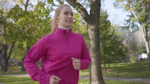 Thumbnail for Smiling Caucasian Woman in Pink Sportswear and Headphones Running in the Autumn Park. Female Runner