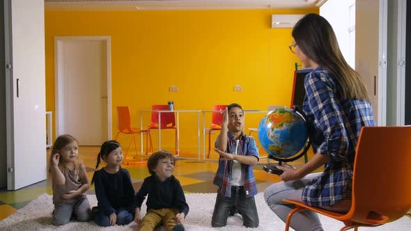 Cover Image for Preschool Kids Studying Globe Together with Teacher