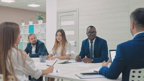 International Team of Businessmen Discusses Company Plans. Dark-skinned Businessman Listens