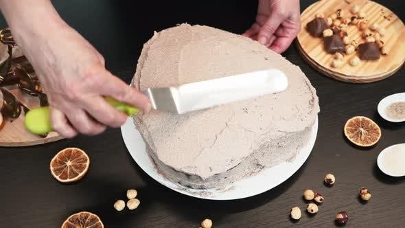 Female confectioner prepares cream cake.