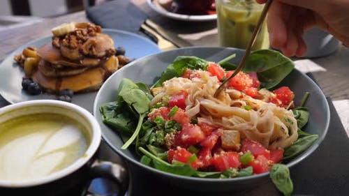 Eating Warm Pasta Salad with Leaves and Vegetables. Healthy Delicious Vegan Brunch Outside. Stack of