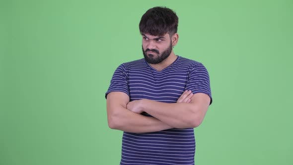 Thumbnail for Angry Young Overweight Bearded Indian Man with Arms Crossed