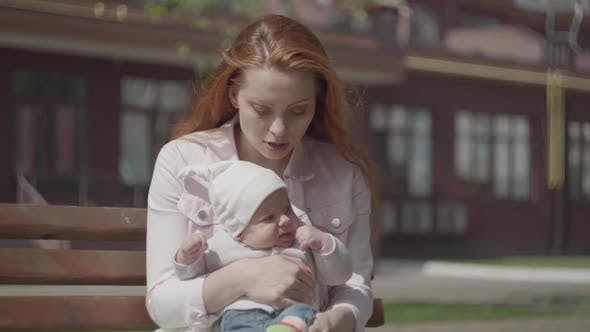 Cover Image for Portrait of a Beautiful Red-haired Woman Playing with Her Child Sitting on the Bench Close-up. The