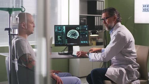 Mature Oncologist Explaining CT Image To Patient During Chemotherapy