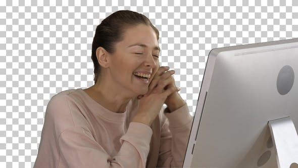 Thumbnail for Woman watching videos on computer and laughing, Alpha Channel