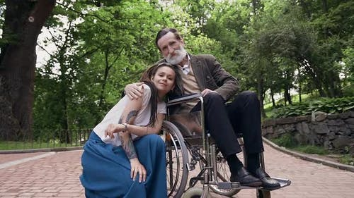 Trendy Woman and Her Sedentary Contented Respected Bearded Old Granddad in Wheelchair