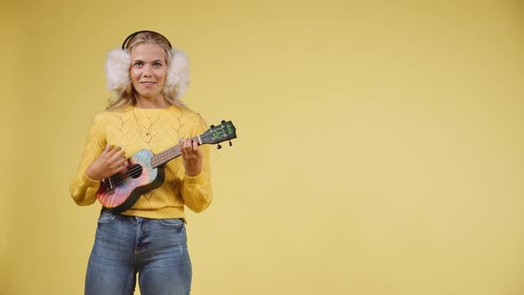 Thumbnail for Artistic Young Woman Playing the Ukulele While Wearing Fluffy Earphones