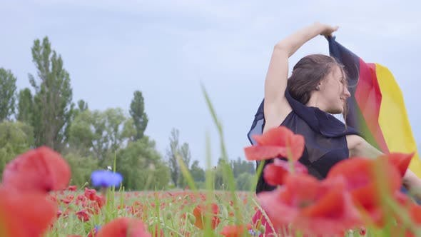 Thumbnail for Cute Adorable Young Woman Dancing in a Poppy Field Holding Flag of Germany in Hands Outdoors