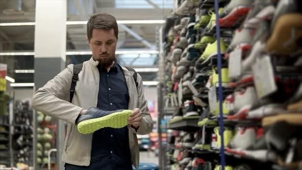 Male Customer is Taking Sport Shoes From Rack in a Sport Hypermarket