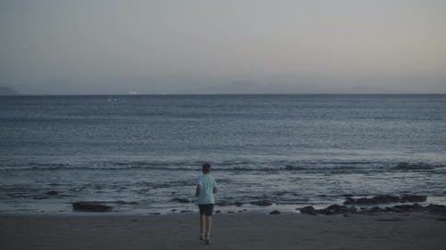 Child throwing stones into the ocean. Black sand beaches of Canary Islands