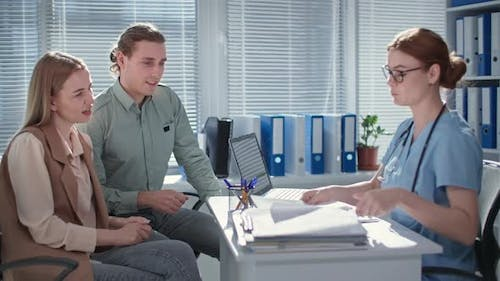 Married Couple Enjoying Good Tests During Consultation with Female Doctor in Hospital Office