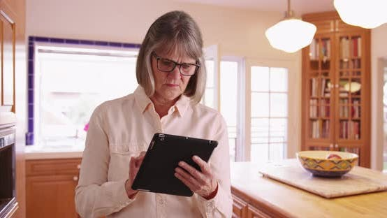 White mature lady using pad device indoors in domestic kitchen setting