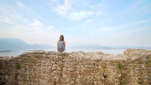 Girl Sitting on the Bricks Looks at the View to Lake Garda
