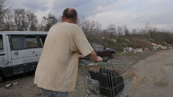 Thumbnail for Back View of Male Pushing Shopping Cart at Landfill