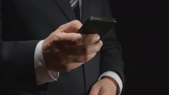Thumbnail for Businessman Holds A Smartphone By Hand And Types On It