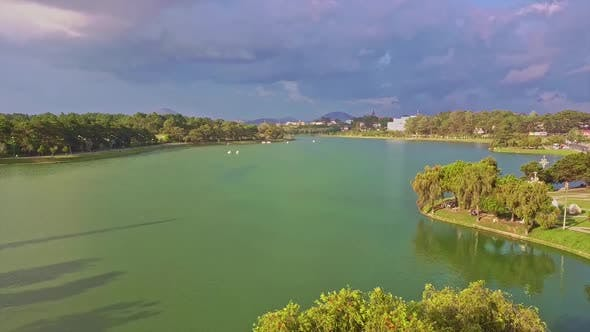 Thumbnail for Flycam Removes From Tranquil Green Lake with Island