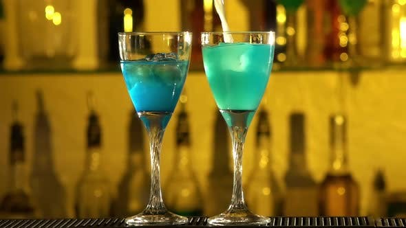 Thumbnail for Barman Puts Cubes of Ice Into a Glass, Pouring Three Different Alcohol Liquids, Turquoise, Using