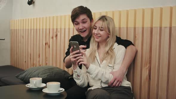 Thumbnail for Glückliches Paar mit Smartphone zusammen und Lachen in Cafe