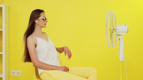 Young Woman Is Chilling Out In Front of Electric Fan