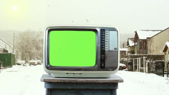 Old TV with Green Screen on Street in the Snow.