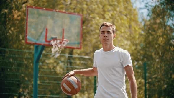 Thumbnail for Ein Mann, der auf einem Sportplatz steht und den Basketballball stopft