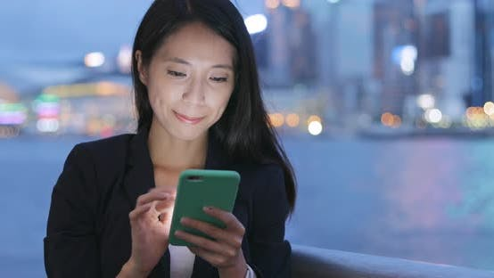 Cover Image for Business Woman Reading on Mobile Phone at Night