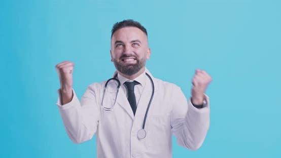 Thumbnail for Ecstatic Mature Medical Doctor Enjoying Success, Gesturing Yes, Blue Studio Background