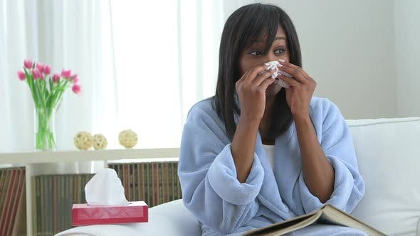 Thumbnail for Black woman with flu, blowing nose into tissue