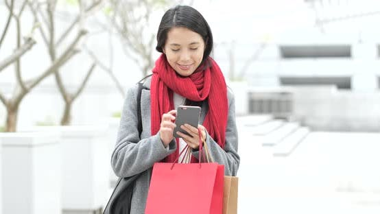 Thumbnail for Shopping woman holding paper bag and use of mobile phone in city