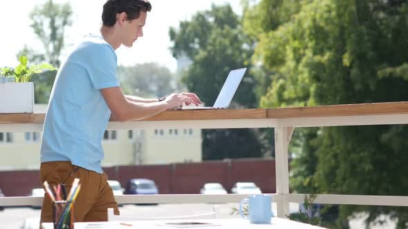 Thumbnail for Sunny Day, Man Standing and Typing on Laptop in Balcony