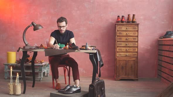 Thumbnail for Serious Cobbler Engaging in Shoe Making Process. Young Man Sets Up Business.